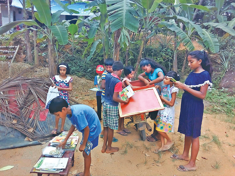 Children look to borrow books from his mobile library. AP/RSS